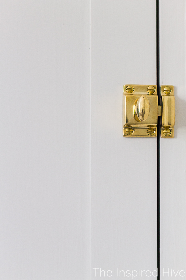 Unlacquered brass latch in vintage style on shaker cabinet door
