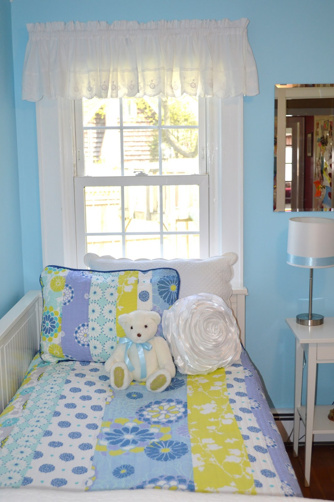Blue bedroom for girls with teddy bear and floral pillow