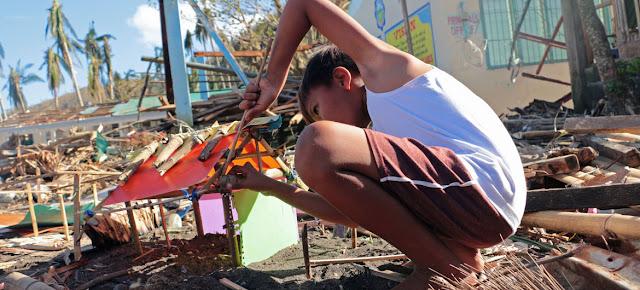 Un niño construye una casita con basura y escombros. Su hogar fue completamente destruido con el paso del Tifón Goni en las Filipinas.UNICEF/Nino Luces
