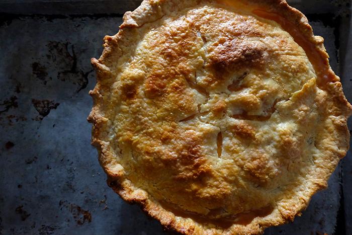 baked peach pie on baking sheet