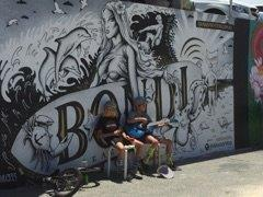 Young entrepreneurs trying to make some money in front of Bondi beach graffiti wall
