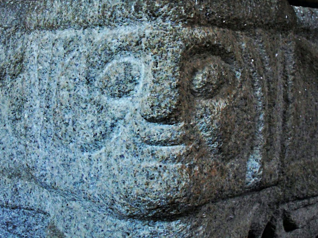 Carved heads on the font at St.Symphorian churchm Veryan, Cornwall