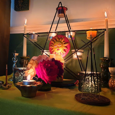 Green paneled wall, yellow altar cloth, pentagram candle-holder with sun plaque, home grown roses. Two green candle-holder jars. goddess shaped incense burner at the back. Two taper candles in green holders. The altar is a mostly symmetrical arrangement. Three incense sticks in a pentacle shaped flat incense burner.