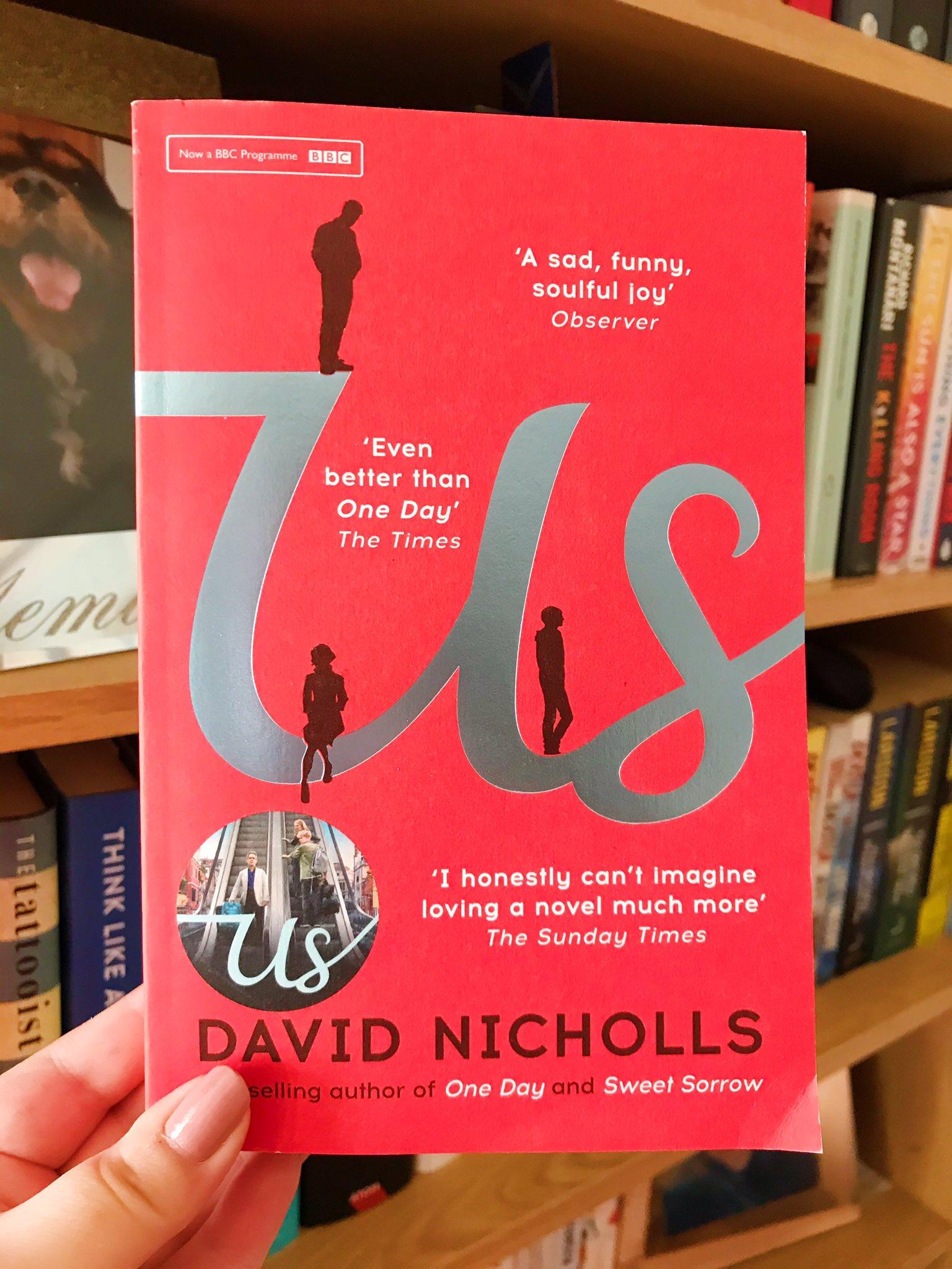 Us by David Nicholls held up in front of bookshelf