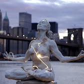 a sculpture in a yoga pose and glowing at cracks that line her body