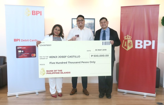 "Kenji Castillo (center), one of the lucky winners of BPI's ""Get Ready to Win"" raffle promo, claims his check worth Php 500,000 from BPI Debit Cards Product Head Ranjit Okoye (left) and BPI Division Head Raul Dimayuga (right). Castillo says BPI, aside from being his preferred bank, helps him manage his family savings."