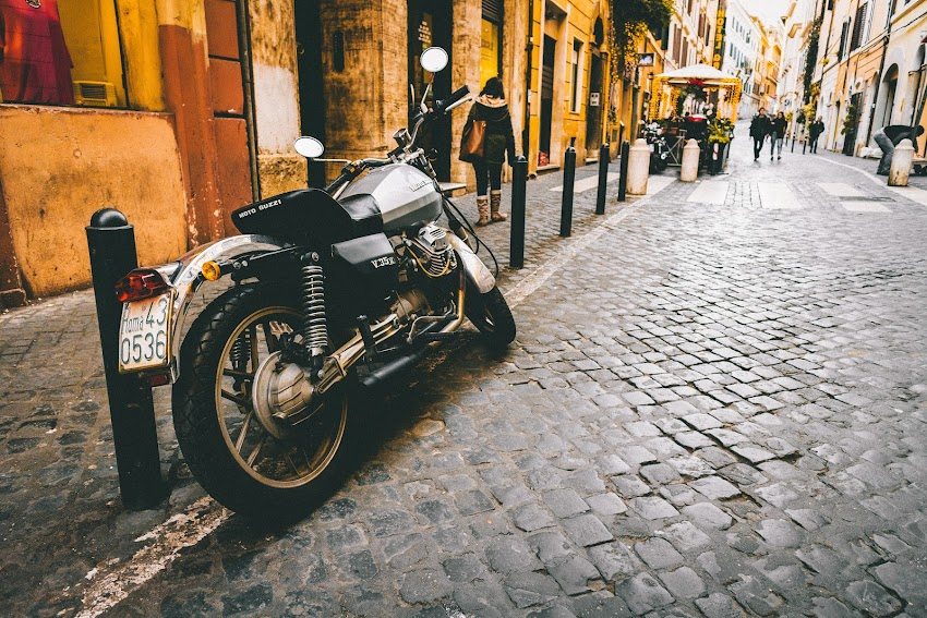 Photograph of Motorcycle Parked Beside Park Bars Near Woman Walking Through Street