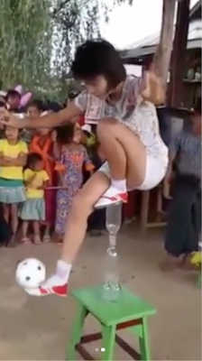 Young Lady Jogs Ball While Standing On Bottles