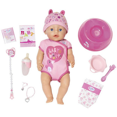 Flatlay of a Baby Born doll in pink clothing, surrounded by a selection of pink accessories.