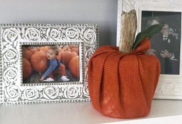 Orange burlap pumpkin next to framed photo of baby with pumpkin.