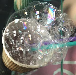 Apparition de bulles suite au fait de souffler dans les gobelets à l'aide de paille contenant la préparation pour réaliser la peinture à bulles