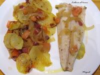 Lubina al horno con patatas, cebolla, tomate y jamón