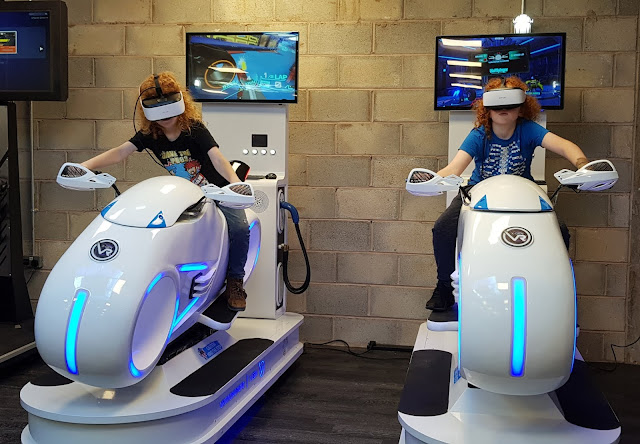 Two boys sitting on VR Bike Racing at X-Gen VR Review stockport