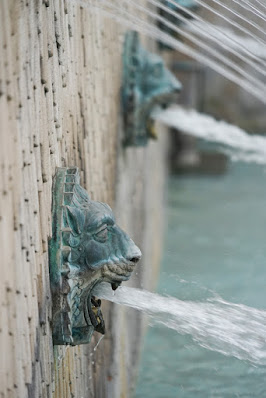Photograph showing detail of a textured concrete wall with bronze lion heads attached, each spouting water from its mouth. One lion head fills the foreground; another is visible but blurred behind it, and more thin streams of water stream above them.