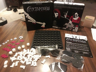 The box and components on display. The box top (the artwork represents an arm holding a bloody axe) and bottom (with artwork showing three players playing the game; two are wearing blackout glasses and the third is placing one of the other player's hand on the board) are standing behind the components: an eight by eight grid of round holes, several white plastic pieces, a small deck of cards, some cardboard tokens, the rules book, and four pairs of blackout glasses.