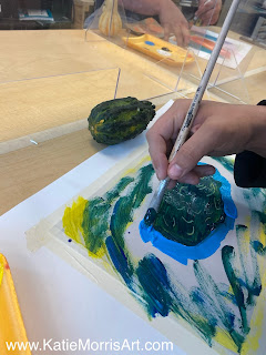 A student's hand painting a gourd