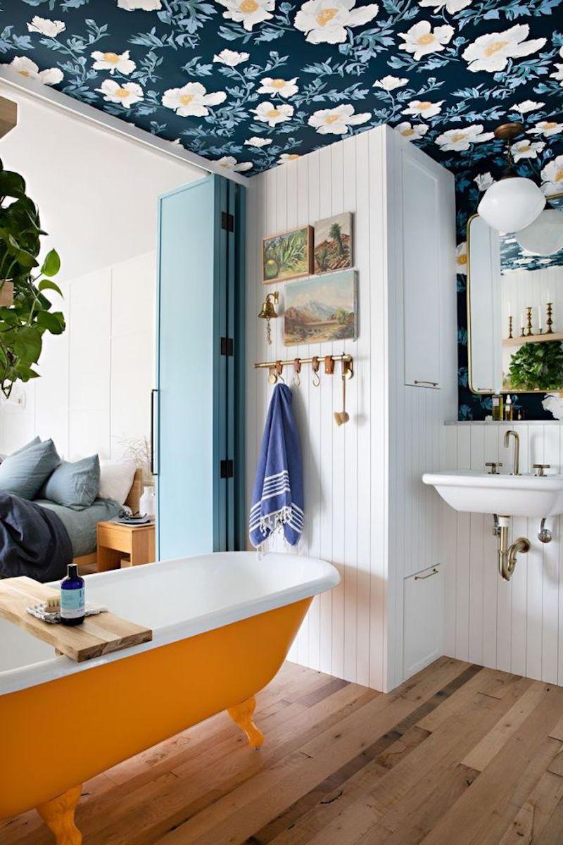 Baño rústico  con papel pintado de flores en el techo y bañera exenta