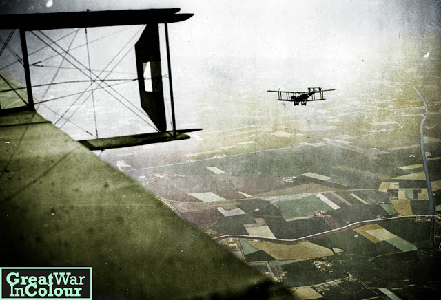 Colorized WWI British bombers on a mission at the Western Front, 1918 from Great War in Colour. Photo taken mid-flight, looking over farmland with biplane in the distance. Dogfight and other stories of pilots. marchmatron.com