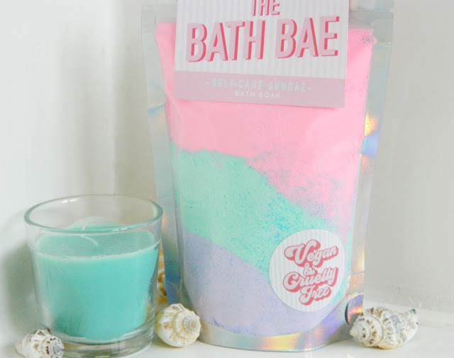 a photo showing a bag of pastel coloured bath soak powder in pink, mint and lilac shades. There is a mint coloured candle and a few seashells surrounding the product, which is from The Bath Bae shop