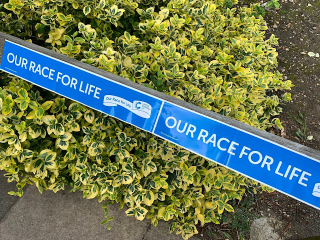 banner saying our race for life up in a school playground