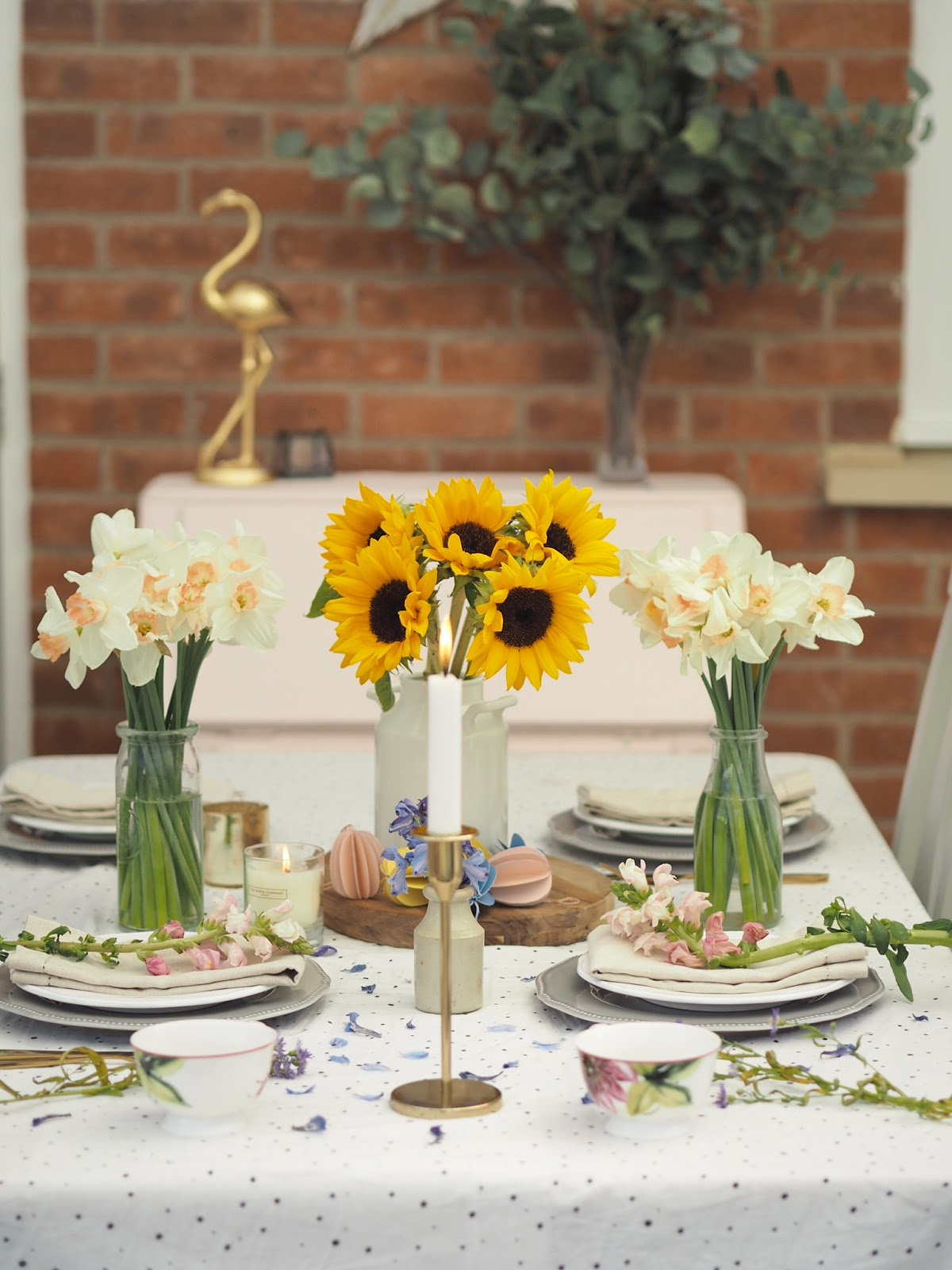 Simple ways to decorate your dining table in your home for Easter. Ideas for spring decorations, and table settings from fresh flowers, to twig trees, and DIY paper decorations with a pretty pastel colour scheme. Inspiration for styling your home for Easter Sunday lunch on a budget, and using things you can find laying around at home.