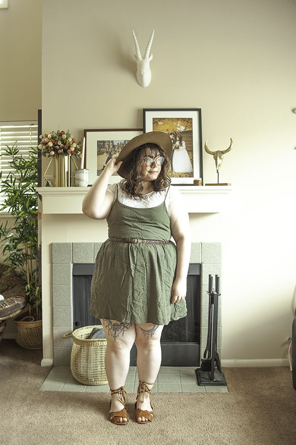 An outfit consisting of a brown panama hat, white lace short sleeve blouse, an olive green spaghetti strap short dress and brown corset lace up sandals.