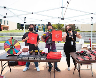 three participants holding free merchandise at Skyline College Hour