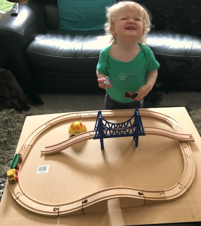toddler-grinning-by-train-set