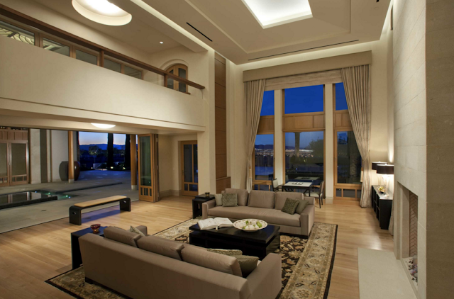 Melongok ke bagian dalam, ruang tamu didominasi oleh warna putih. Sementara sofa berwarna abu-abu, beberapa furnitur lain menggunakan warna hitam.