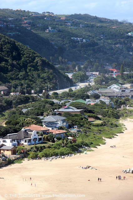 Beach houses with lush green hills in the background, in Wilderness in South Africa.
