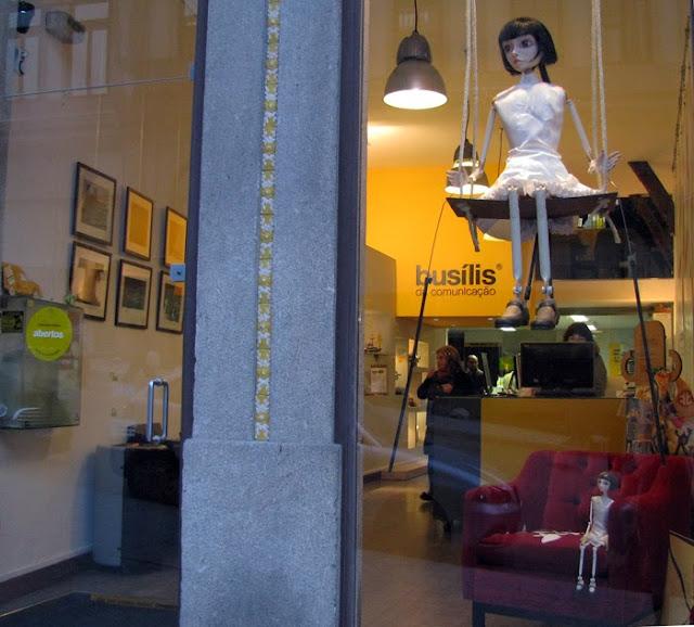 Montra da Busilis da Comunicação com uma marioneta num baloiço