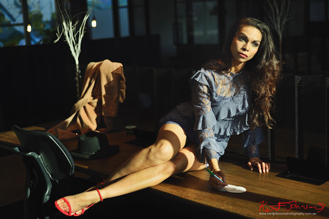 Full length shot of model sitting across a desk with beautiful long legs in direct light for a modelling portfolio. Photographed by Kent Johnson, Sydney, Australia.