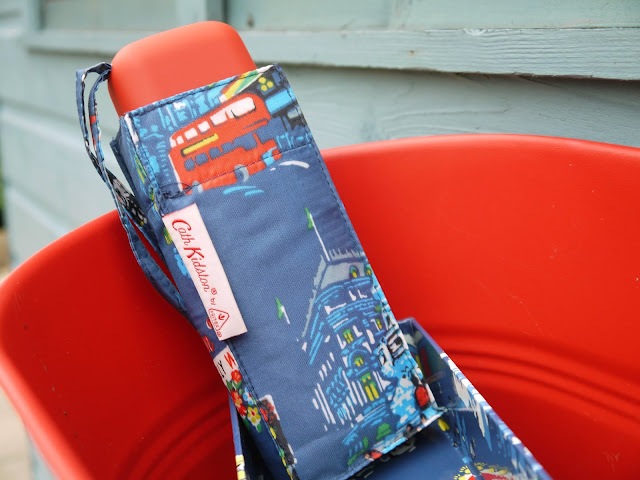 a blue umbrella sits in a red tub on a blue background. the umbrella is printed with london scenes such as red buses.