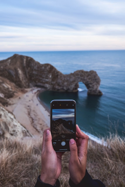 fotografer sedang membidik landscape dengan kamera hp