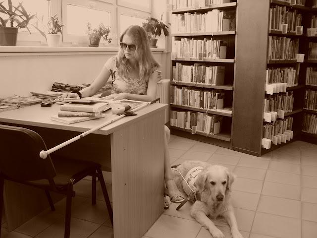 Linda sedí za stolem v knihovně, zlatý retrívr Cilka leží na zemi u stolu