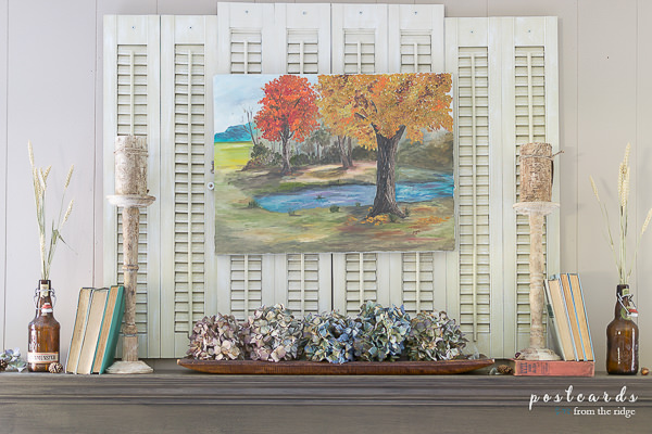 vintage fall themed oil painting on mantel