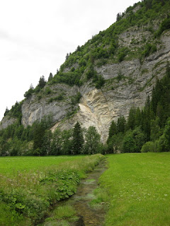 Creek flowing through the valley near granite hillside near La Tsintre, Switzerland