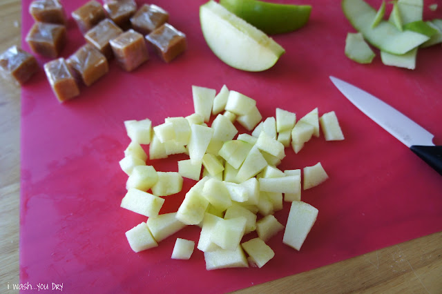 Chopped apple on a cutting board next to apple sliced and wrapped caramel squares.