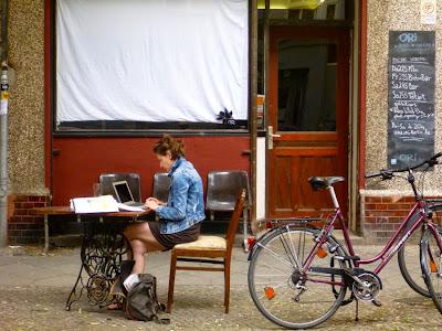 Vor einem zugehängten Schaufenster sitzt eine junge Frau an einem Tisch auf der Straße