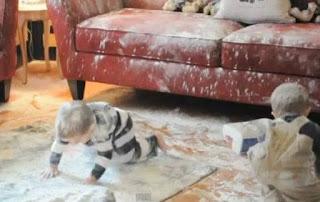 Niños tiran polvo detergente por todo el sofá tele