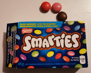 An open box of Canadian Smarties (chocolate) with three pieces (red, brown, and pink) laying out