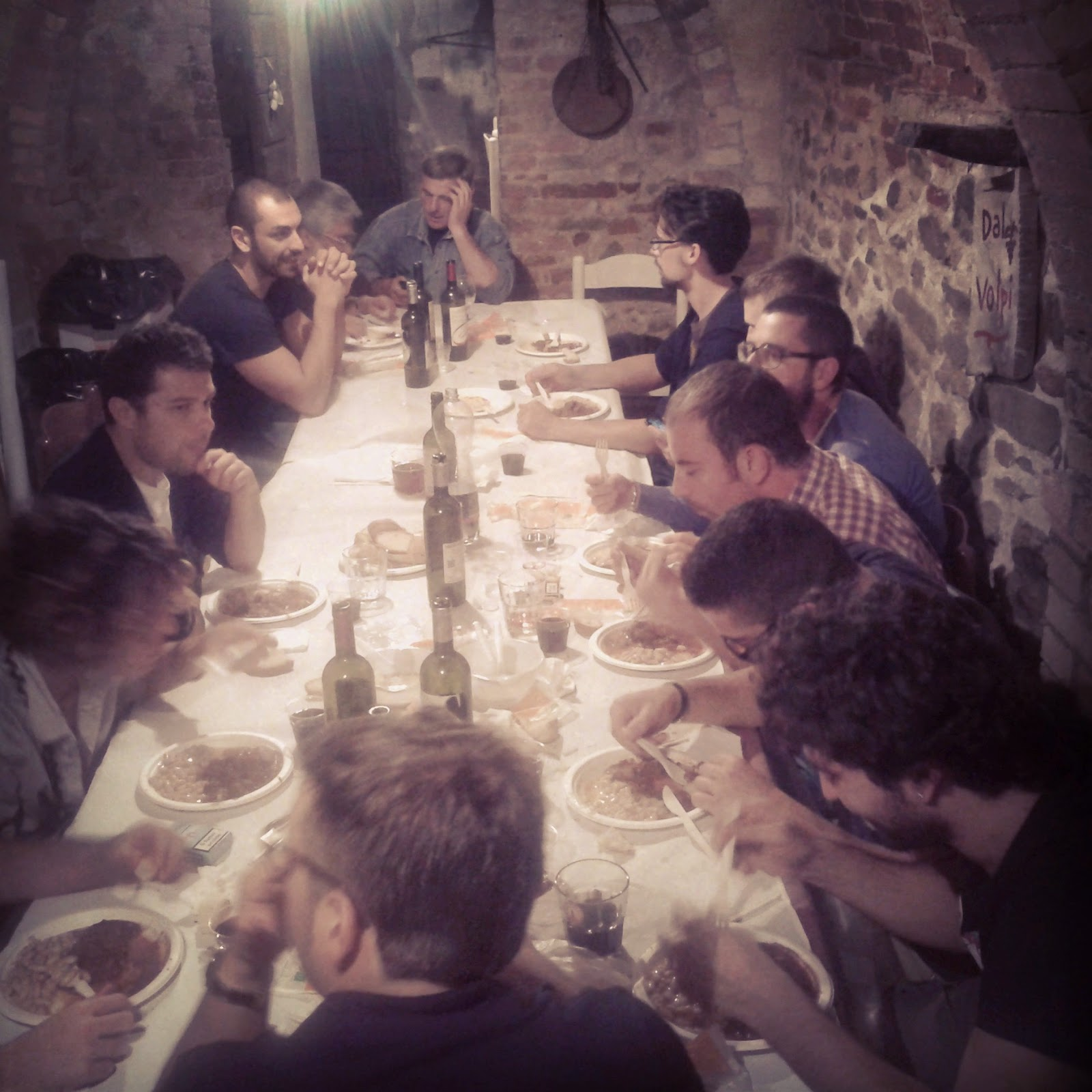 a long table filled with people in an old Tuscan cellar used as restaurant