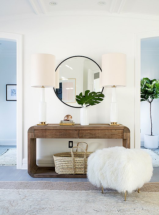 Modern farmhouse decor in a mid-century modern home. A few notes of family-friendly design: rounded edges on the console, a Moses basket (perfect for a sleeping baby or a pile of blankets), and a Tibetan fleece stool that takes soft to a new level.