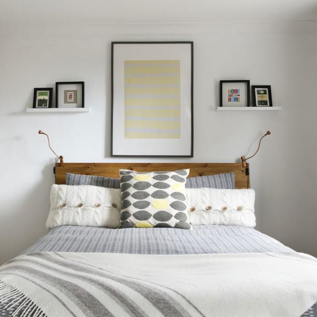 Kamar tidur putih kecil dengan lampu dinding kecil di kedua sisi tempat tidur dan dua bingkai foto kecil