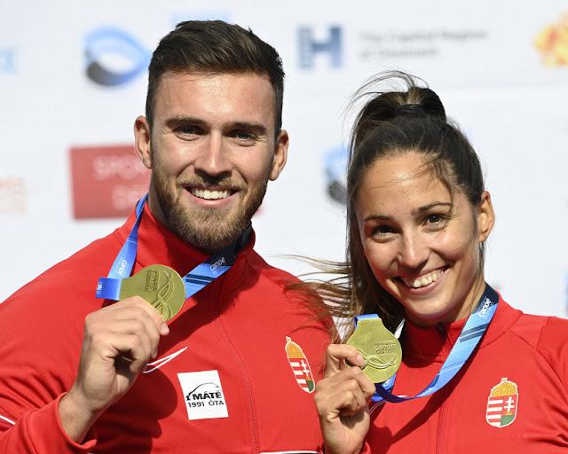 Anna Lucz e Kolos Csizmadia sorriem e mostram medalha de ouro