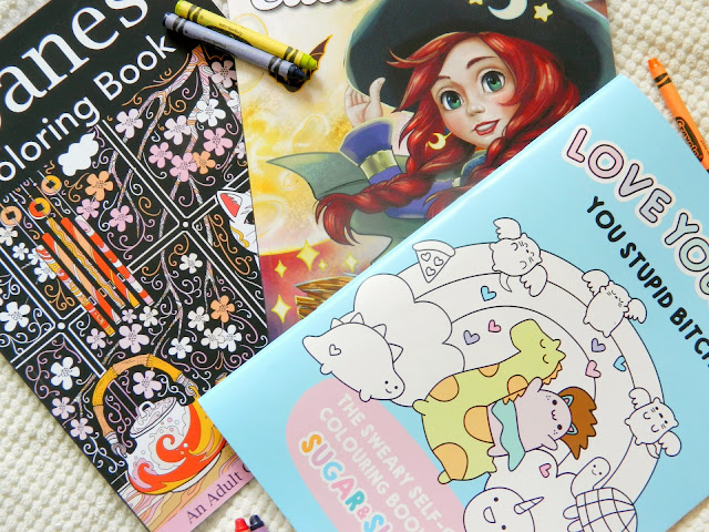 A photo of three colouring books, surrounded by crayons and gel pens