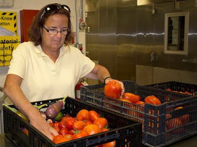 Nancy Haney check out tomatoes from the Tri-County garden (photo provided by Tri-County)