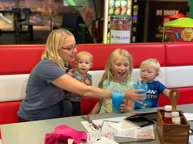 Me looking hassled in an american style diner holding the baby and sitting next to my 2 daughters who are messing around with slush style drinks