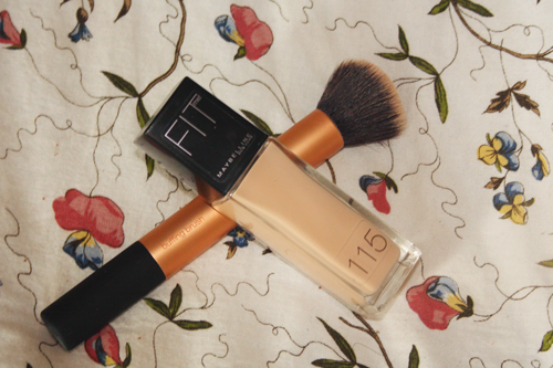 maybelline fit me foundation lying on a bed alongside a real techniques buffing brush