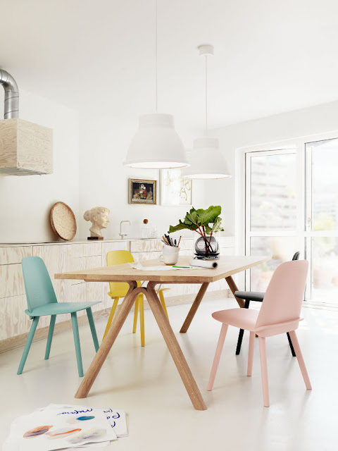 bright dining room with wood table, mismatched pastel and colored chairs, wood cabinets and white pendant lights
